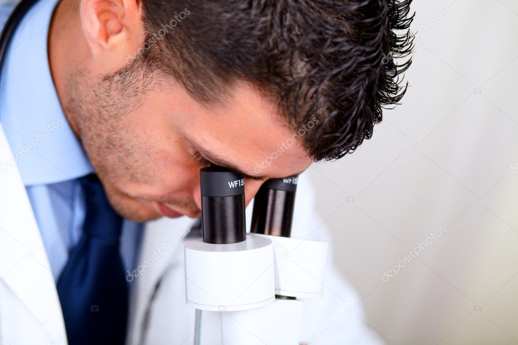 Closeup portrait of a Professional medical man using a microscope — Stock Photo #11421774