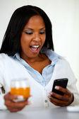 Donna giovane sorpresa leggendo un messaggio sul cellulare — Foto Stock