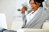 Surprised woman holding plenty of cash money — Stock Photo