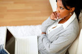 Pensive young woman is sitting on the floor — Stock Photo