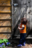 Little girl looking at a locked door — Stock Photo