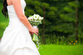 Bride in dress with flowers without the face — Stock Photo