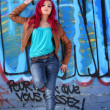 Pink hair girl against a blue wall — Stock Photo
