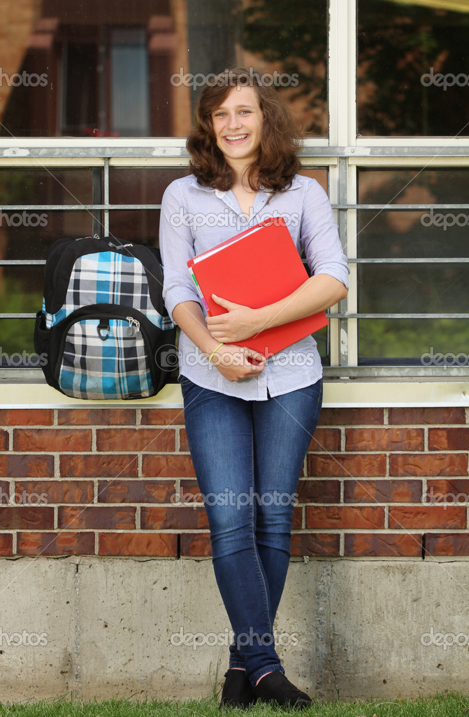 Smiling girl standing against a wall of her school — Stock Photo #11713874