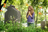 Girl praying at the cemetery — Stock Photo