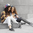 Two young  skateboarding girl friends looking at pictures on phone — Stock Photo