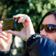 Dark Haired Woman Taking  A Photo With Cellphone - Stock Photo