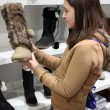 A young brunette Woman shopping for boots — Stock Photo