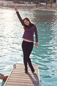 молодой счастливая девушка, стоя на пирсе — Стоковое фото