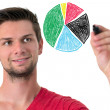 Stock Photo: Young man drawing a pie chart