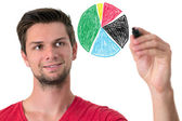 Young man drawing a pie chart — Stock Photo
