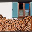 Stack of logs in front of the window — Stock Photo