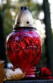 Red glass ever-burning on tomb in cemetery — Stock Photo