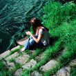 Young woman sitting on the riverbank - Stock Photo