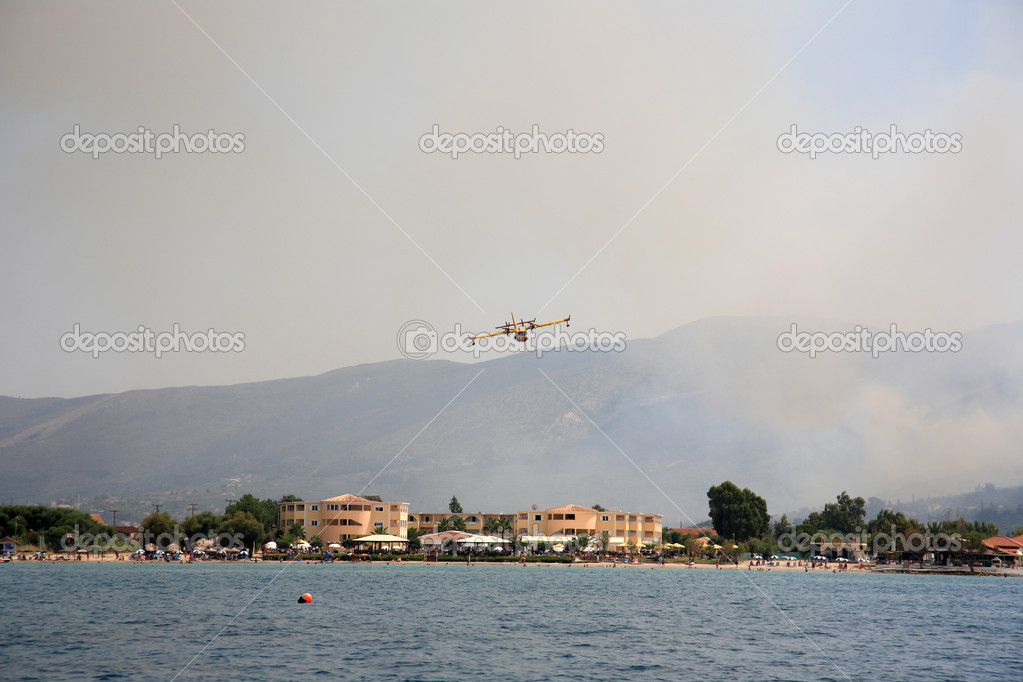 ZAKYNTHOS, GREECE- AUG 1: Canadair CL-415 or Bombardier 415 approaching the sea to take water during big fire at the mountain close to the village Alykes, August 01, 2012 Zakynthos, Greece — Stock Photo #12122283