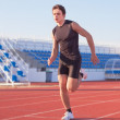 A young man starts running in the stadium. Treadmill. — Stock Photo