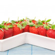 Red Strawberries in a porcelain dish. Closeup. On a white backgr — Stock Photo