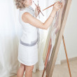 Painter draws a picture on the easel. — Stock Photo