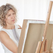 Stock Photo: Beautiful artist paints a picture.