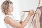 Målare målar en bild med penslar. — Stockfoto