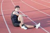 Ein junger athlet macht dehnen. vor dem hintergrund der treadm — Stockfoto