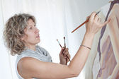 Woman artist draws a portrait of a woman. In the studio. — Stock Photo