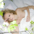 Sexy woman lies on a bed in the wood — Stock Photo