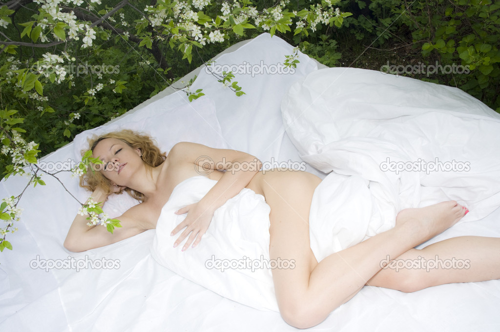 Sexy woman lies on a bed in the wood, sleeping — Stock Photo #10973849