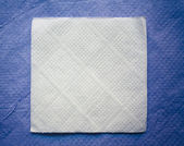 Paper napkin on blue napkin background — Stock Photo