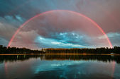Full rainbow over the lake — Stock Photo