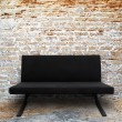 Modern sofa in old brick wall room - Stock Photo