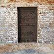 Old wooden door on brick wall - Stock Photo