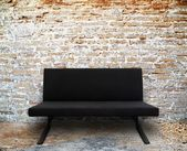 Modern sofa in old brick wall room — Stock Photo