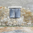 Stone wall with wooden window shutter - Stock Photo