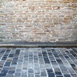 Foto Stock: Brick wall and cobblestone street