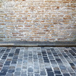 Brick wall and cobblestone street — Stok fotoğraf