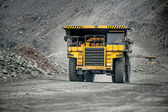 Yellow mining vehicle driving in the pit — Stock Photo