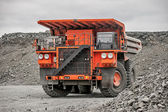 Orange mining vehicle driving in the pit — Stock Photo