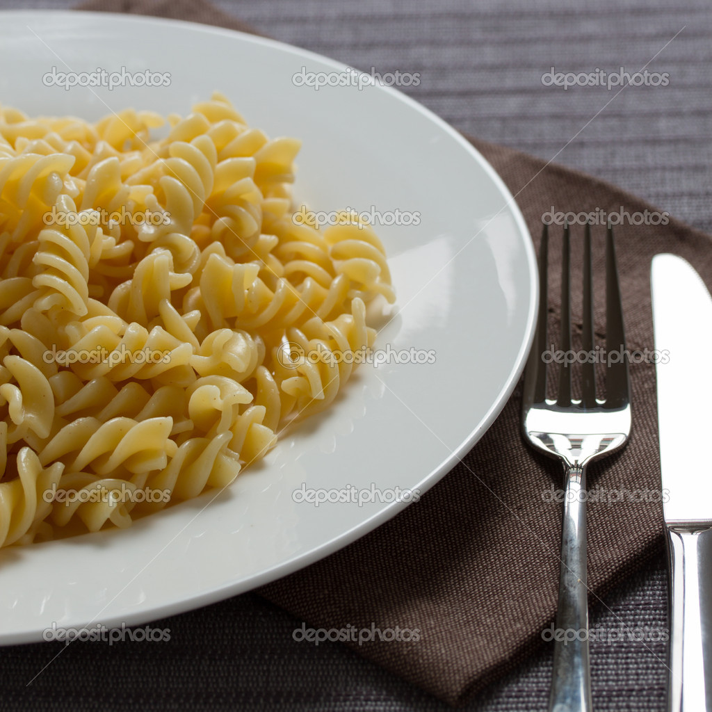 A plate with cooked pasta fusilli with fork and knife — Stock Photo #11941393