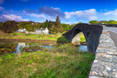 Ancient bridge in a village by the river — Стоковое фото