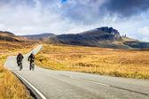 在通过一个荒凉的景观公路上骑自行车的人 — 图库照片