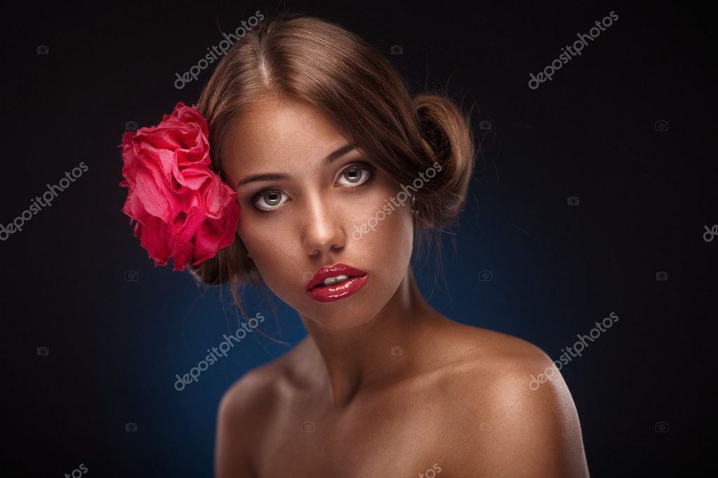 Beauty face of the young woman with flower. Girl on dark blue background — Stock Photo #11227667