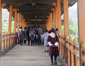 Bhutanese walk across the bridge of the Punakha Dzong (Bhutan) — Stock Photo