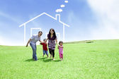 Cheerful family with a drawn house — Stock Photo