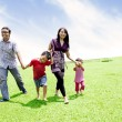 Happy asian family in meadow — Stock Photo #10989581