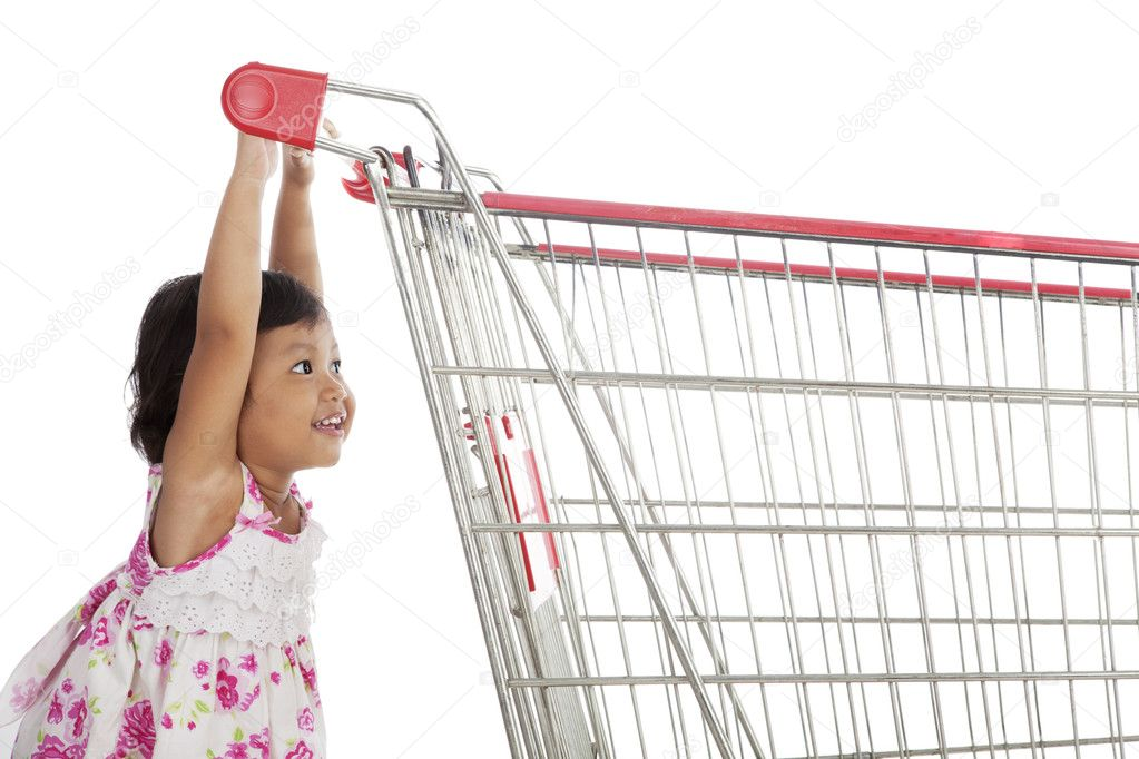 Cute little asian girl pushing trolley shot in studio isolated on white  Stock Photo #10987942