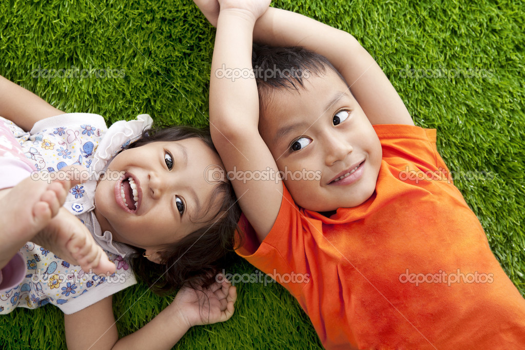 Cute happy asian siblings lying on the green grass shot at meadow — Stock Photo #10988596