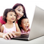 Happy family using laptop — Stock Photo