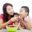 Mother and children eating fruit salad — Stock Photo #11061773
