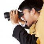 Shocked businessman looking with binoculars — Stock Photo